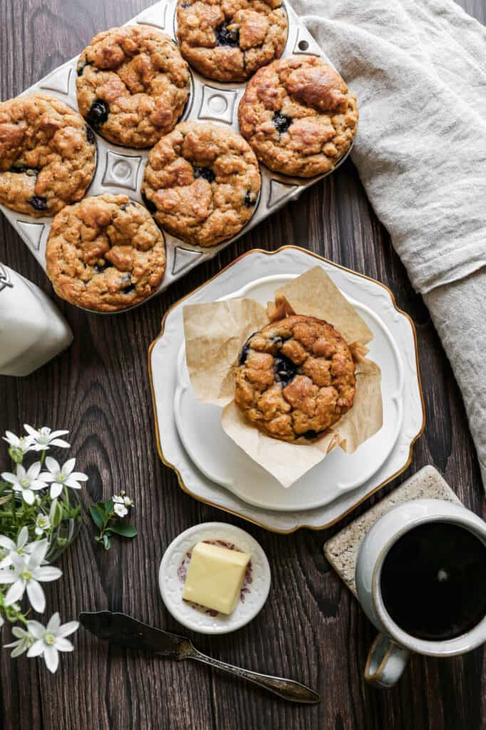 a small white plate with a gluten free blueberry oat muffin sitting next a muffin tin with six muffins and a bottle of milk