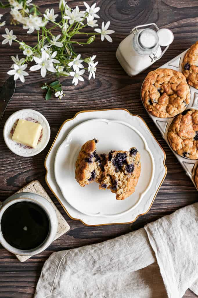 a gluten free blueberry oat muffin broken in half on a white plate next to a bottle of milk and a small plate with a pat of butter