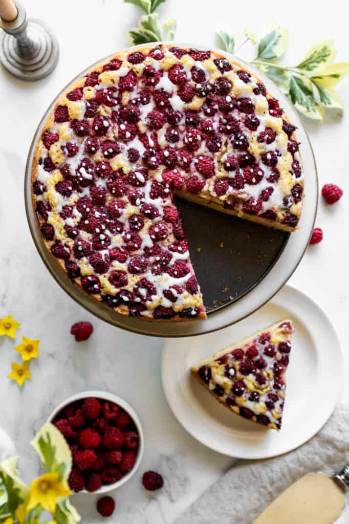 a gluten free raspberry cornmeal cake on a cake stand with a slice on a white plate with a bouquet of yellow flowers next to it