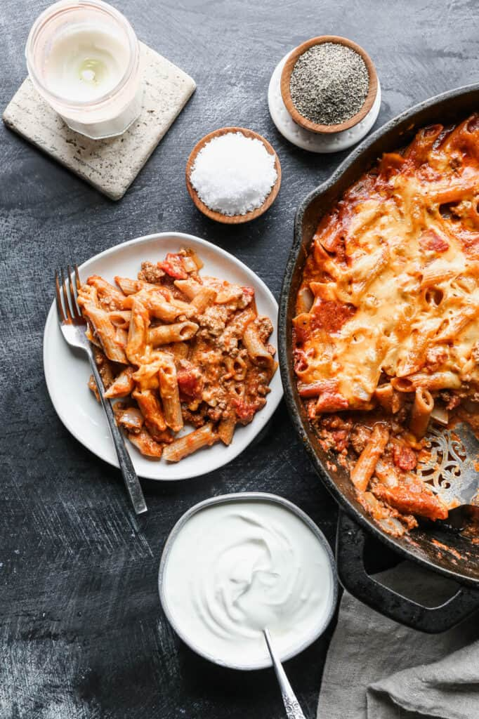 a cast iron skillet and a small white plate of gluten free taco pasta bake with a pinch bowl of salt and pepper and a bowl of sour cream