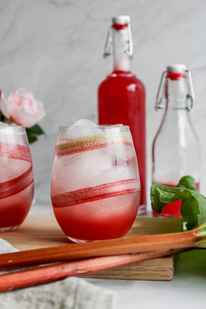 a glass lined with a slice of rhubarb and ice with a instant pot rhubarb simple syrup and sparkling water