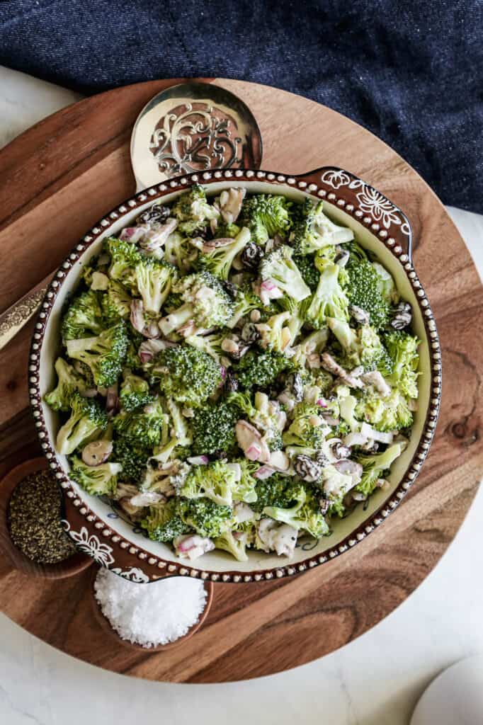a bowl of sugar free broccoli salad on a wooden platter with a silver serving spoon next to it