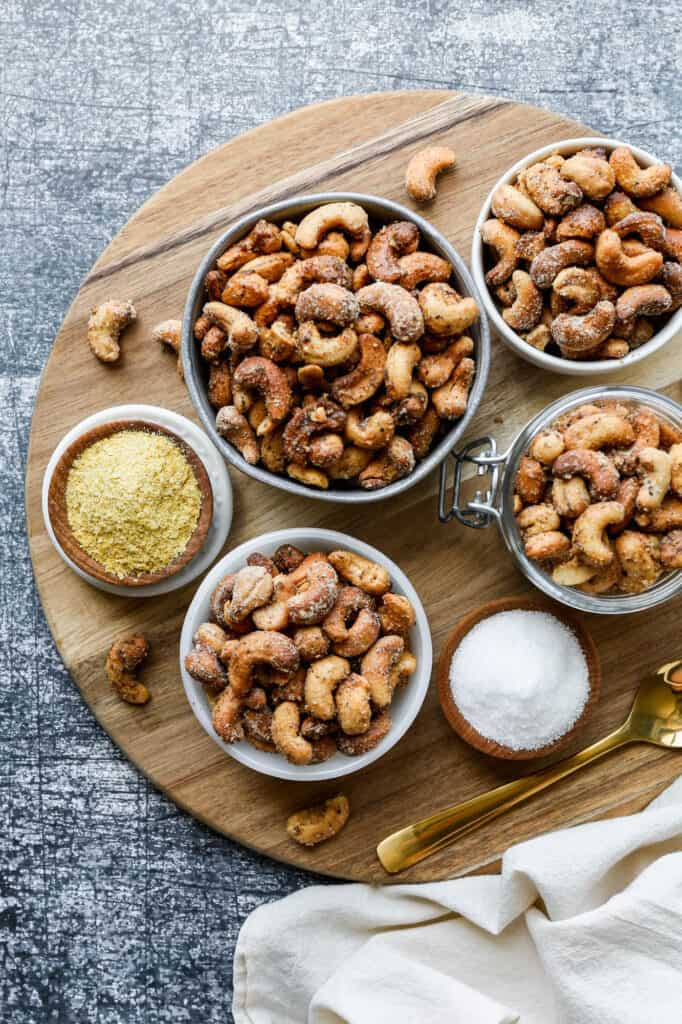 small bowls of air fryer salt and pepper roasted cashews on a round wooden cutting board
