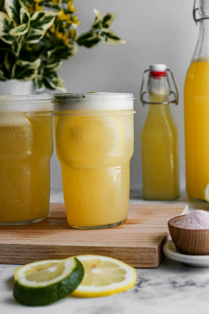 a ball canning jar with lemon lime homemade sports drink with ice cubes and lemon and lime slices
