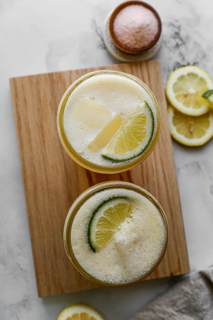 Two glasses of lemon lime homemade sports drink with ice and lemon wedges on top sitting next to a small bowl of pink salt