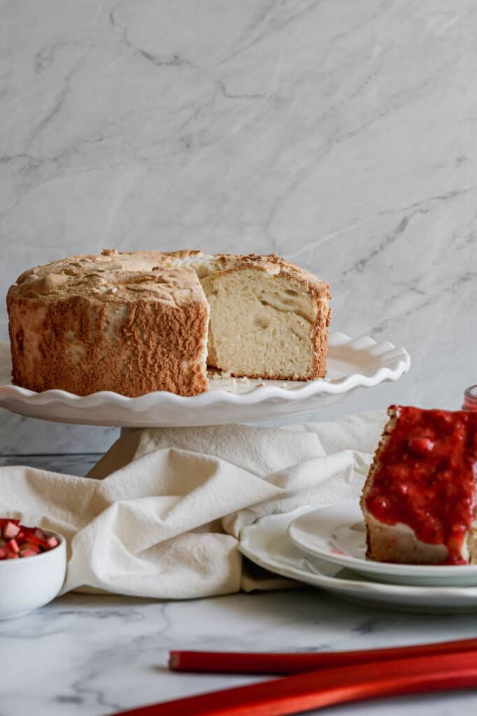 a gluten free angel food cake on a white cake stand next to white plates, a silver serving knife and a glass jar of strawberry rhubarb sauce
