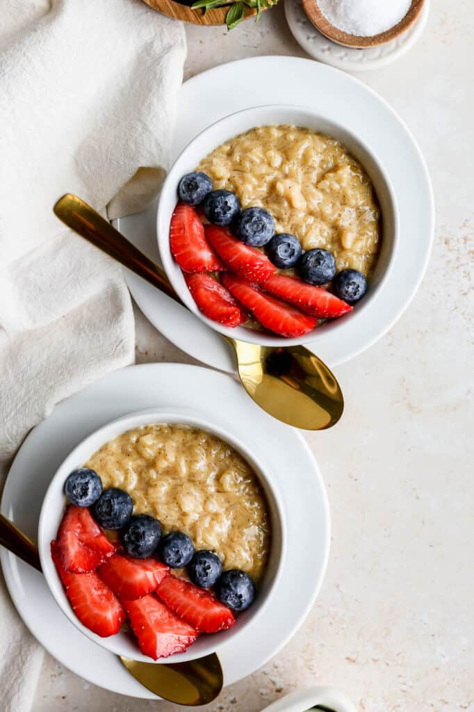 a white bowl of gluten free instant rice pudding with fresh blueberries and strawberries on top.