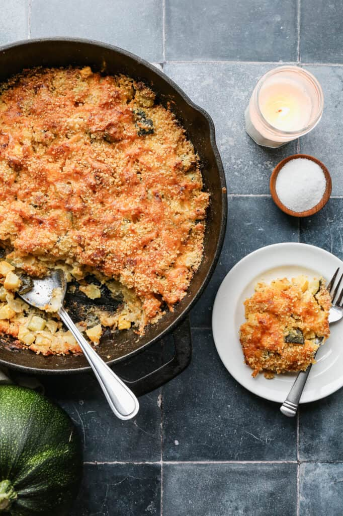 a cast iron skillet of gluten free summer squash casserole with some served onto a white plate