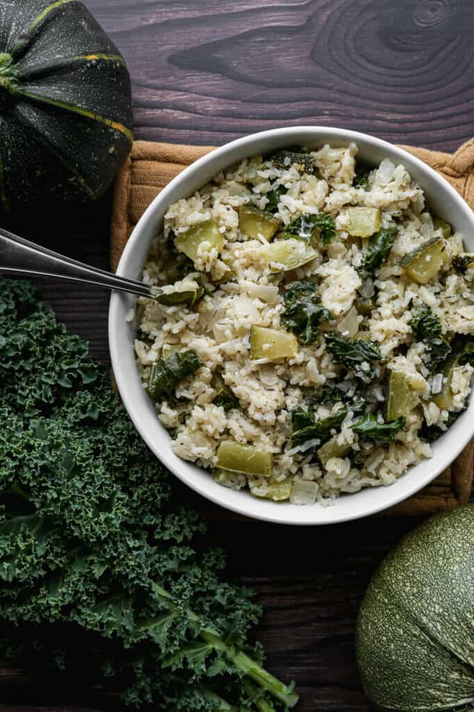 a white bowl of gluten free baked kale and zucchini pilaf on a tan oven mitt next to two round zucchini and some kale leaves