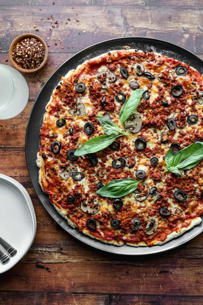 a gluten free pizza crust topped with sauce, cheese, mushrooms, black olives, basil and turkey chorizo on top
