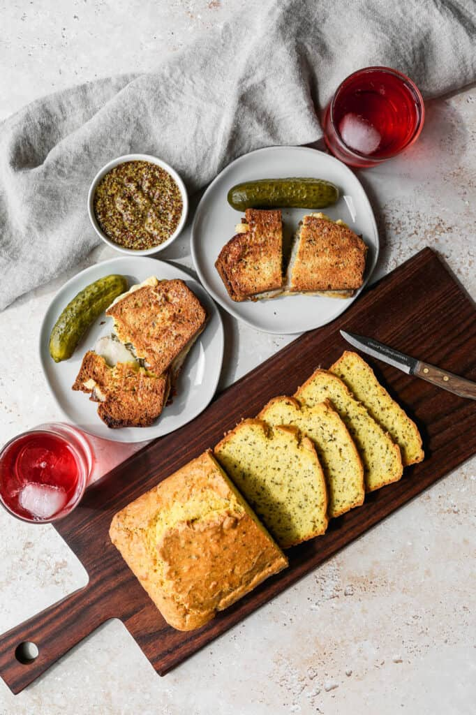a wooden cutting board with a loaf of gluten free herbes de provence keto bread with a few slices next to two plates of sandwiches made from the bread