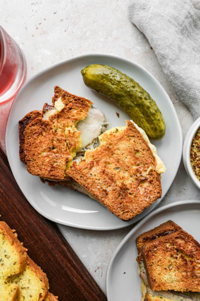 a sandwich made from this gluten free herbes de provence keto bread on a white place with a dill pickle next to it