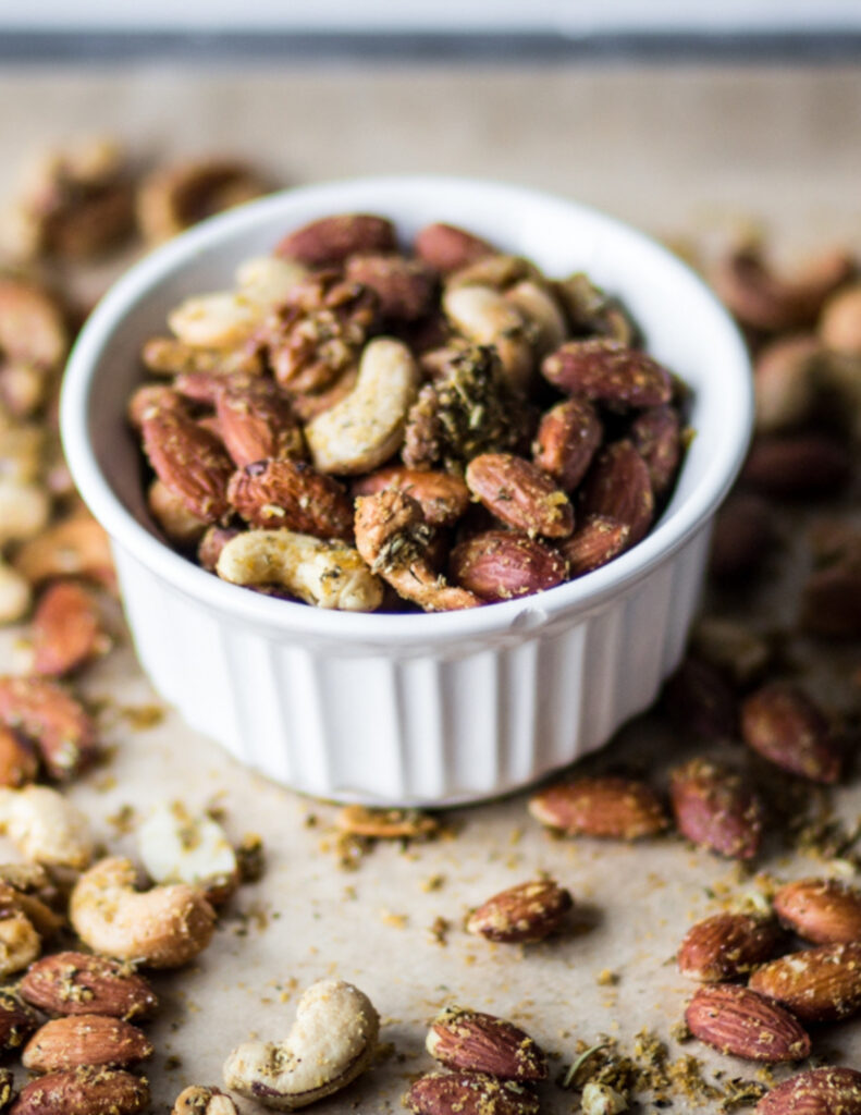 a white ramekin of air fryer savory herb roasted nuts on a parchment lined baking sheet of roasted nuts
