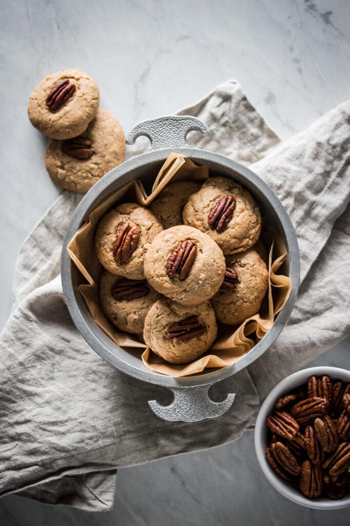 a silver bowl of gluten free butter pecan cookies next to a bowl of pecans on a marble surface