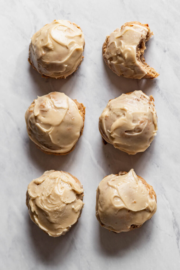 six gluten free apple pie cookies with brown sugar frosting sitting on a marble countertop