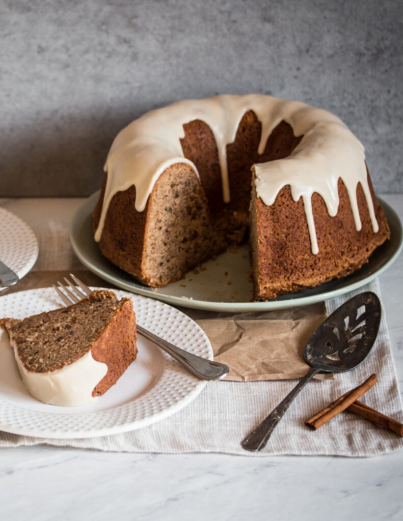 a gluten free cinnamon coffee cake with vanilla glaze on top and a slice of cake on a plate