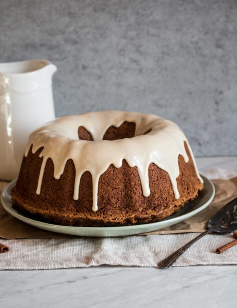a gluten free cinnamon coffee cake with vanilla glaze on a plate