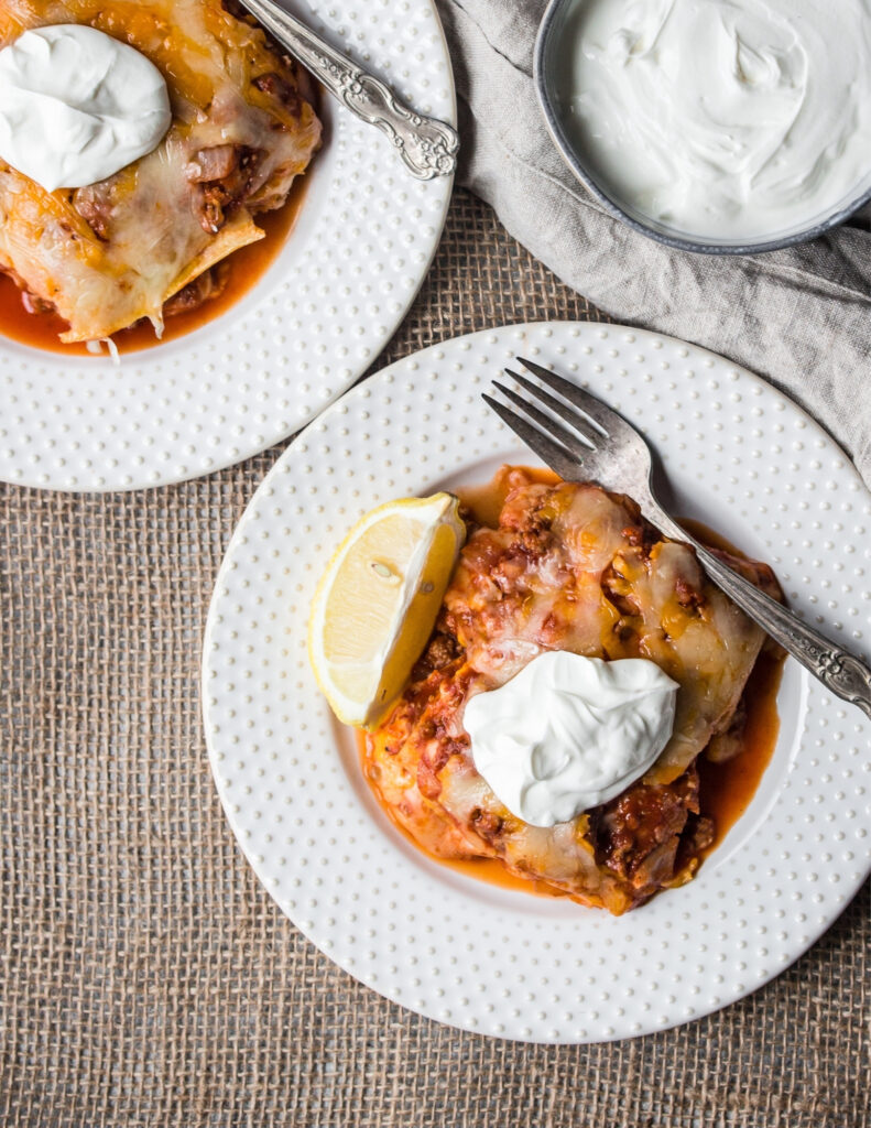 two white plates with servings of gluten free enchilada skillet next to a bowl of sour cream