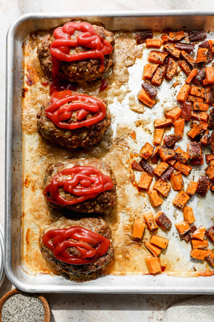 a metal sheet pan of sheet pan meatloaves and sweet potatoes right out of the oven