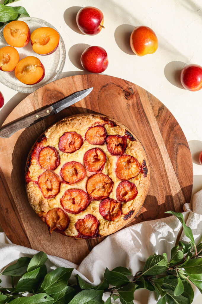 a gluten free plum cornmeal cake on a round wooden platter with fresh yellow plums around it