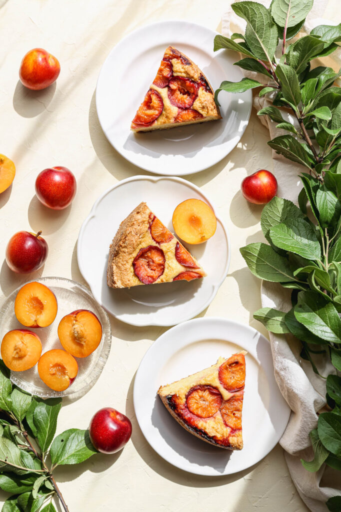 three slices of gluten free plum cornmeal cake on white plates with fresh yellow plums around them