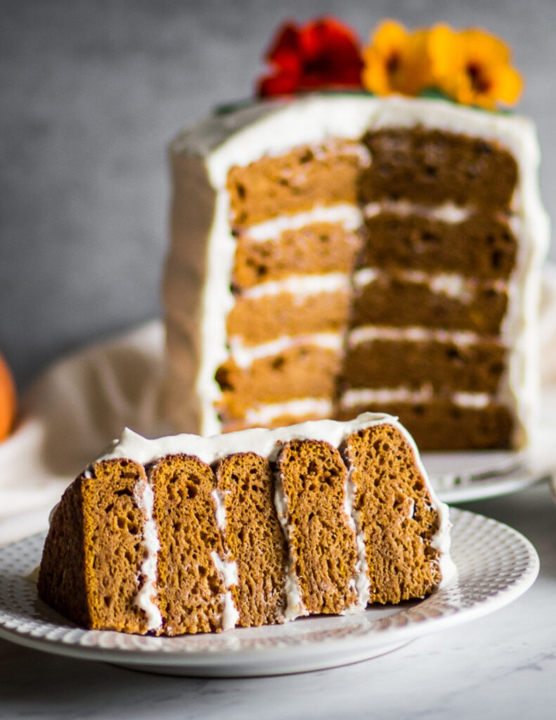 a gluten free pumpkin cake with cream cheese frosting on a plate with a slice and an orange pumpkin next to it