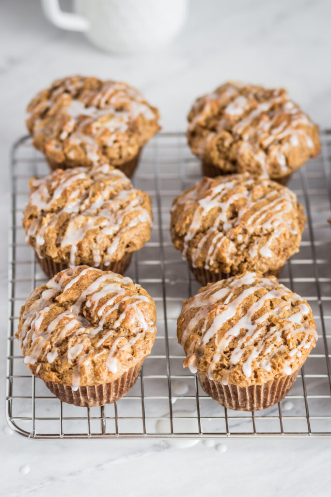 a metal cooling rack of gluten free apple carrot muffins with glaze drizzled over top of them