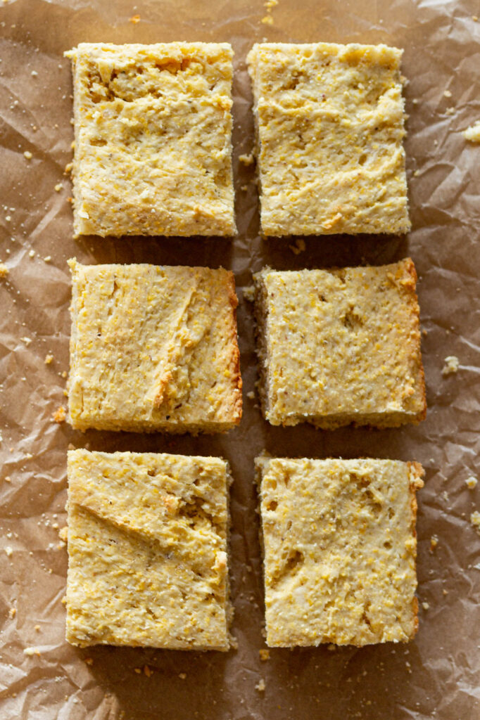 six cornbread squares on natural parchment paper with crumbs around them